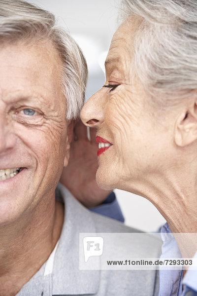Spain  Senior woman whispering into ear of man  smiling