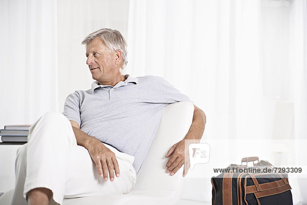 Spain  Senior man waiting in lobby with suitcase