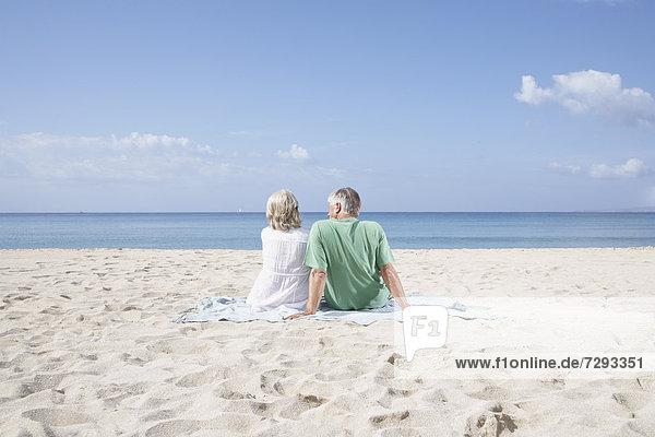 Spain  Mallorca  Senior couple sitting at beach