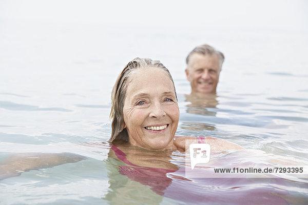 Spanien  Seniorenpaar im Meer schwimmend