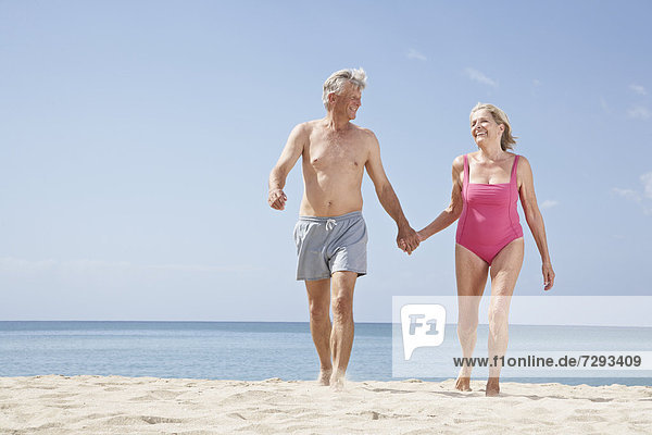 Spain  Mallorca  Senior couple walking on beach