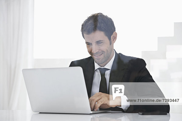 Spain  Businessman using laptop  smiling