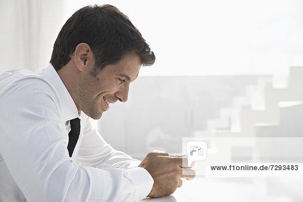 Spain  Businessman using mobile phone  smiling