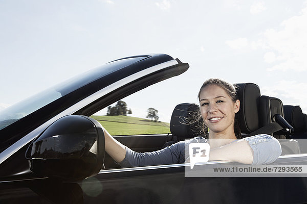 Young woman in car  smiling