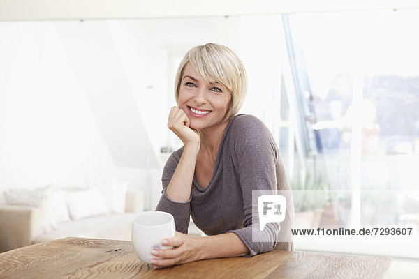 Woman holding cup at table  smiling  portrait