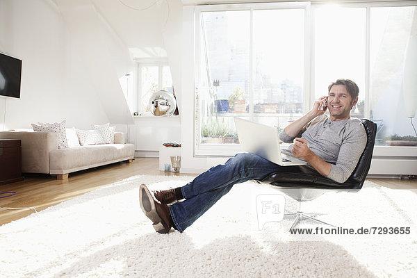 Mann mit Laptop im Wohnzimmer