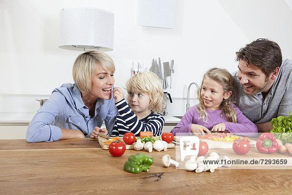 Die Familie bereitet das Essen zu  während der Junge die Mutter füttert.
