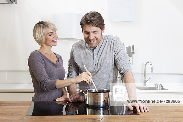 Germany  Bavaria  Munich  Mature couple cooking food in kitchen  smiling