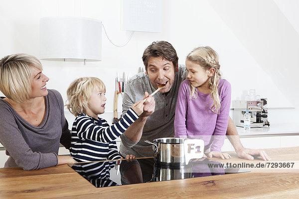 Familie bereitet Essen in der Küche zu  während der Junge den Vater füttert.