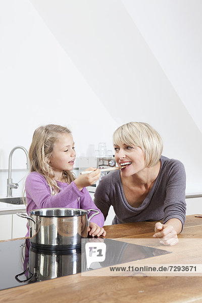 Germany  Bavaria  Munich  Daughter feeding mother in kitchen  smiling