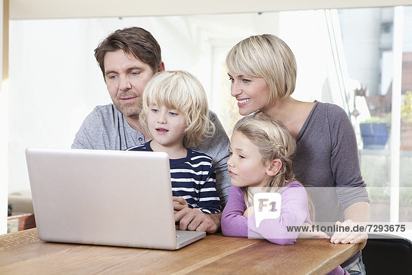 Germany  Bavaria  Munich  Family using laptop  smiling