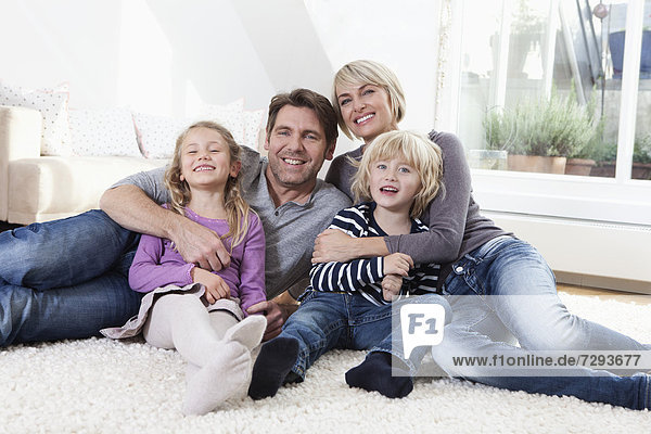 Germany  Bavaria  Munich  Family lying on floor  portrait  smiling