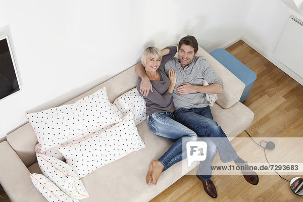 Germany  Bavaria  Munich  Mature couple relaxing on sofa