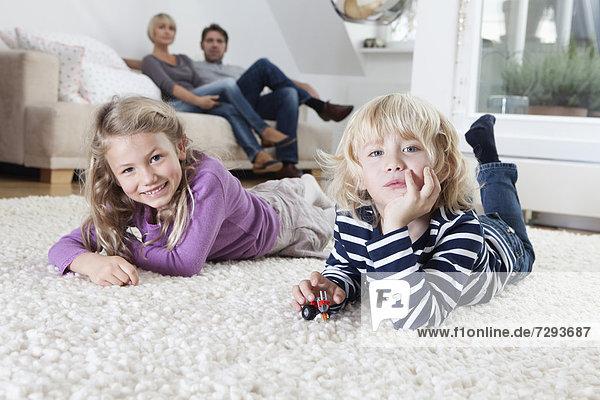 Junge und Mädchen liegen auf dem Boden  die Eltern sitzen auf der Couch im Hintergrund.