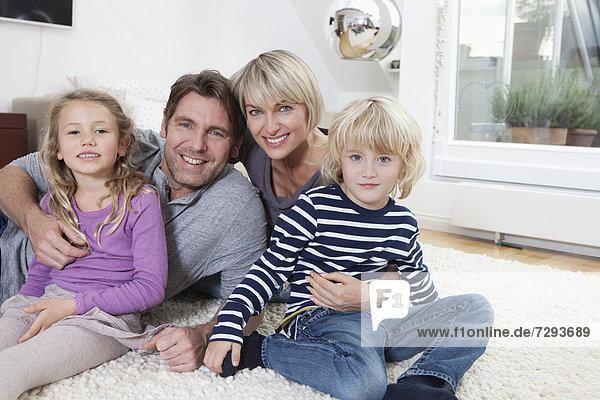 Germany  Bavaria  Munich  Portrait of family lying on floor  smiling