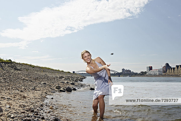 Young woman skipping stones in river