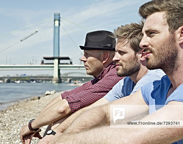 Young men sitting on riverbank