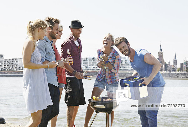 Germany  Cologne  Group of people gathered around barbecue