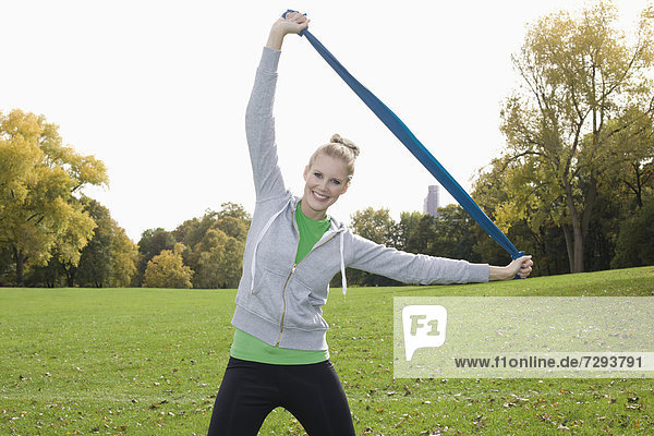 Europe  Germany  North Rhine Westphalia  Duesseldorf  Young woman exercising with belt