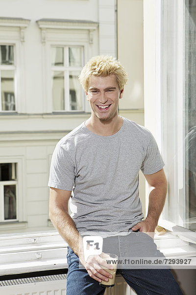 Young man sitting at open window  smiling