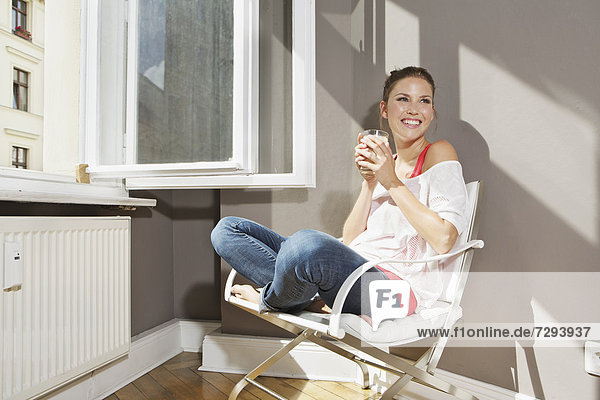 Young woman sitting at open window  smiling