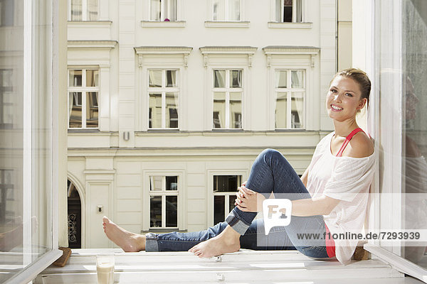 Young woman sitting at open window  smiling  portrait