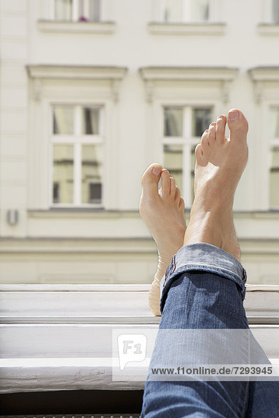 Young woman feets on open window