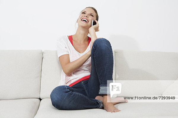 Young woman sitting on couch and using smart phone