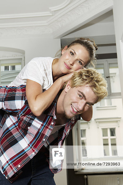 Young man giving piggy back ride to woman