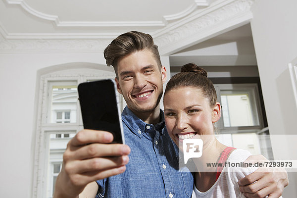 Young man and woman using smart phone  smiling