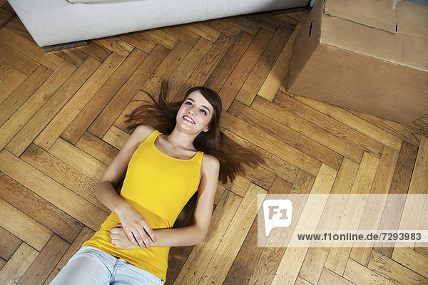 Young woman lying on floor  smiling