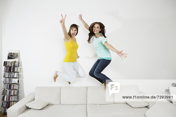 Young women having fun and jumping on couch