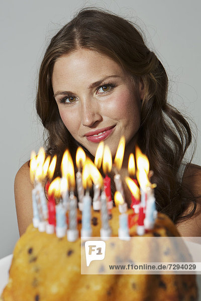 Young woman showing birthday cake  smiling  portrait