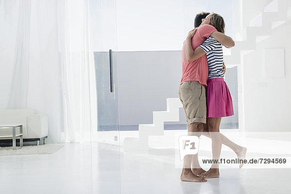 Spanien  Mittleres erwachsenes Paar  das sich in einer modernen Wohnung umarmt