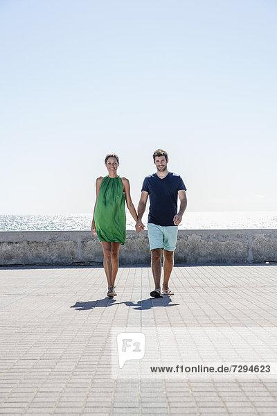 Spain  Mid adult couple walking on pavement