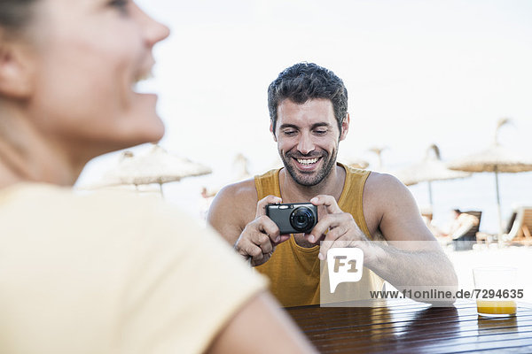 Spain  Mid adult man taking photograph of woman