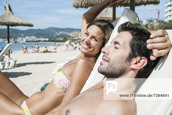 Spain  Mid adult couple relaxing on beach chair