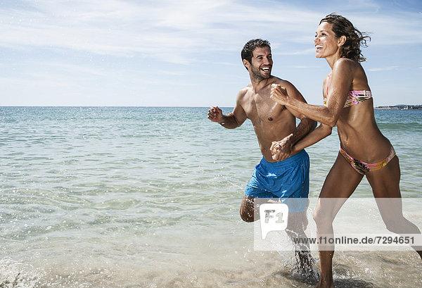 Spanien  Mittleres erwachsenes Paar  das am Strand läuft