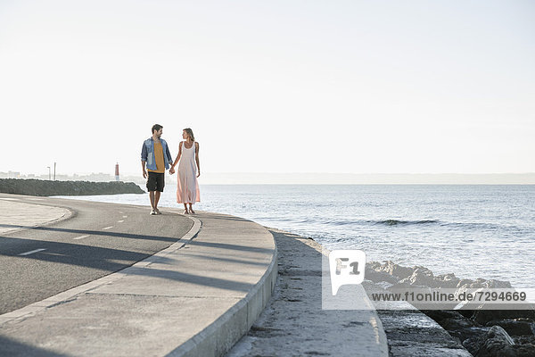 Spain  Mid adult couple walking along coast