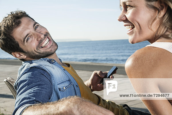 Spanien  Mittleres erwachsenes Paar auf Bank mit Handy