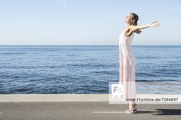 Spain  Mid adult woman standing at Atlantic Ocean with arms out