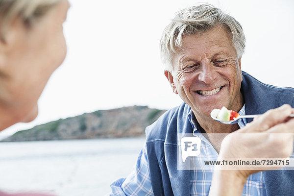 Spain  Senior couple having lunch  smiling