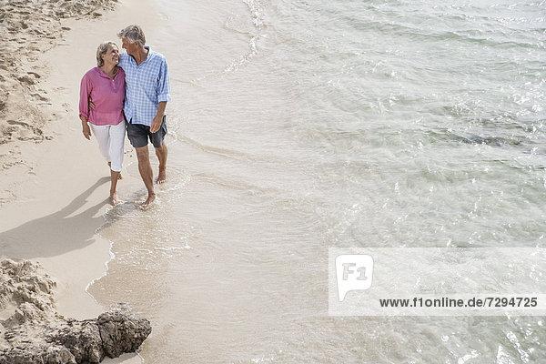 Spain  Seniors couple walking along beach
