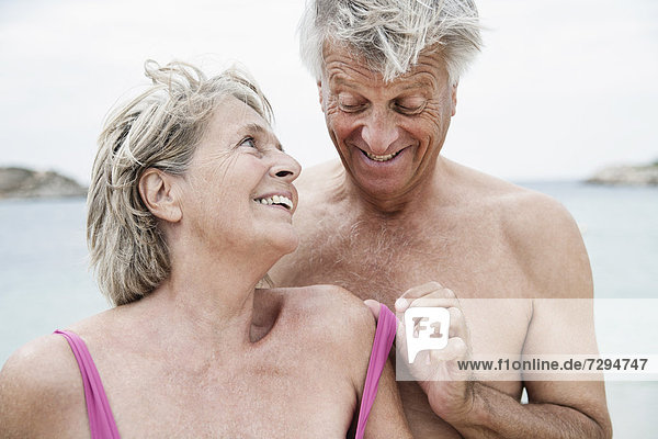 Spain  Senior couple undressing on beach