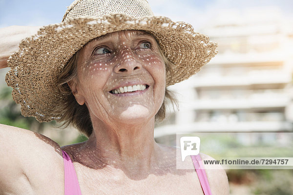 Spain  Senior woman with straw hat  smiling