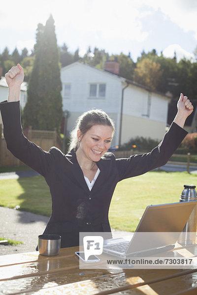 Enthusiastische Geschäftsfrau mit erhobenen Armen beim Blick auf den Laptop