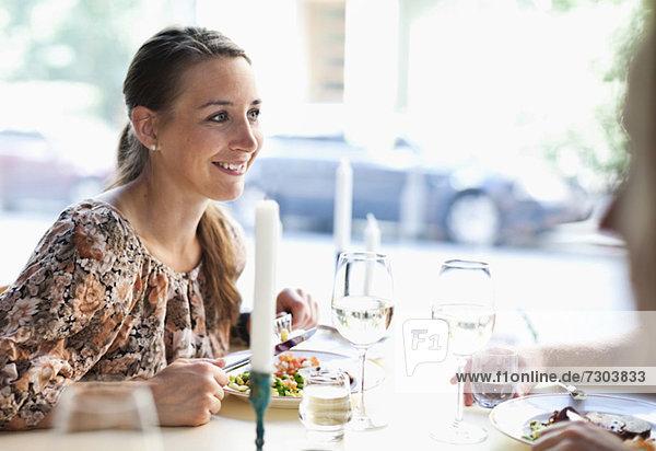 Fröhliche junge Frau beim Anblick eines Freundes am Restauranttisch