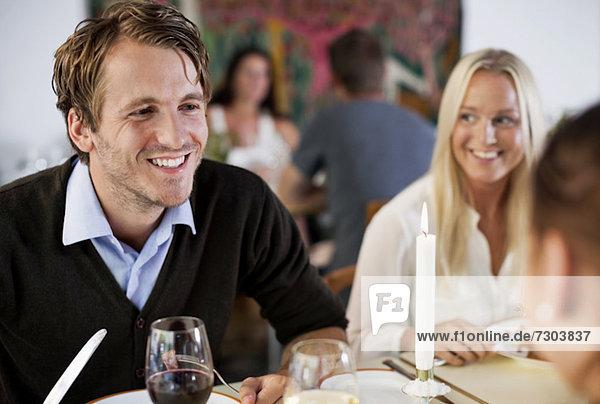 Glücklicher junger Mann mit Freunden am Restauranttisch