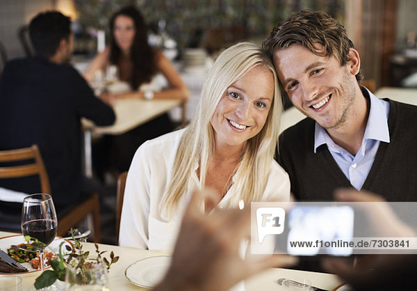 Glückliche Freunde beim Fotografieren im Restaurant