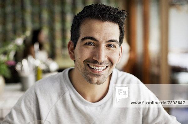 Portrait eines glücklichen jungen Mannes im Restaurant